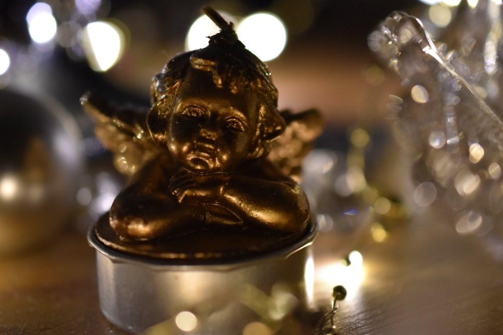 Goldfarbener Engel mit Lichterkette im Hintergrund