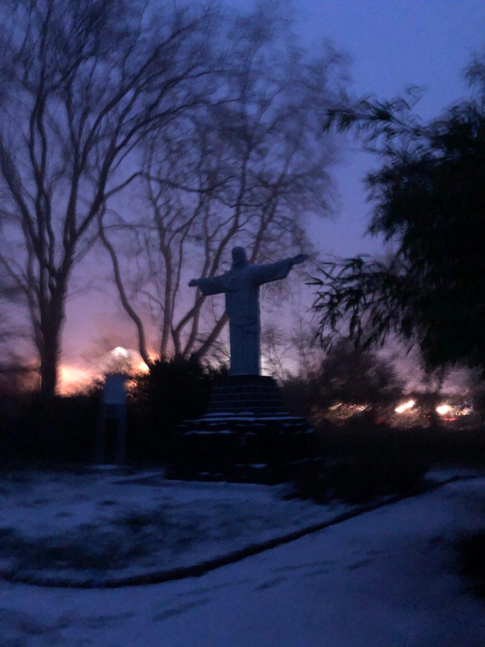 Christus Statue im Licht der Dämmerung im Blumengarten