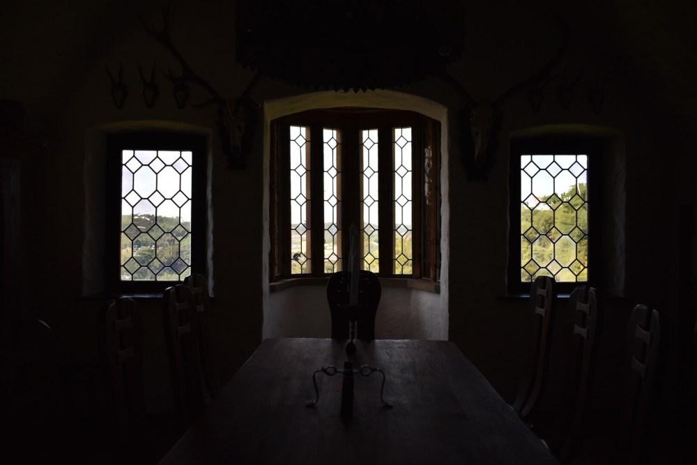 Drei Fenster erleuchten das dunkle Zimmer
