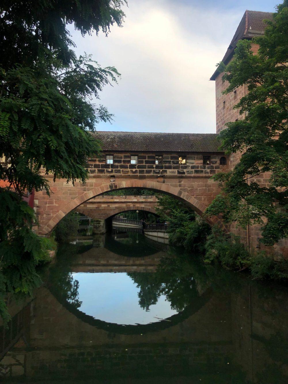 Zwei Brücken spiegeln sich zu zwei Kreisen in der Pegnitz bei der Verteidigungsanlage am Stadtgraben
