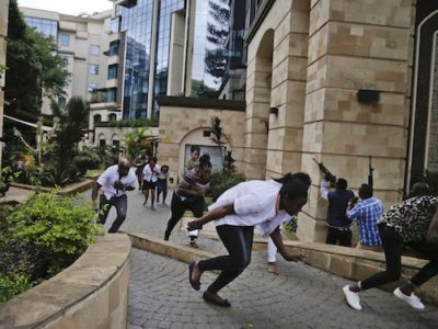 """Civilians flee as security forces aim their weapons at the buildings of a hotel complex in Nairobi, Kenya, on Tuesday. Extremists launched a deadly attack on a luxury hotel in Kenya's capital, sending people fleeing in panic as explosions and heavy gunfire reverberated through the complex. A police officer said he saw bodies, """"but there was no time to count the dead."""" (AP Photo/Khalil Senosi)"""
