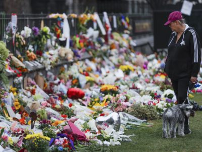 Mourners lay flowers on a wall at the Botanical Gardens in Christchurch, New Zealand, Monday, March 18, 2019. A steady stream of mourners paid tribute at the makeshift memorial to the 50 people slain by a gunman at two mosques in Christchurch, while dozens of Muslims stood by to bury the dead when authorities finally release the victims' bodies. (AP Photo/Vincent Thian)
