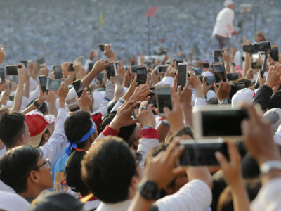 Supporters of presidential candidate Prabowo Subianto and running mate Sandiaga Uno take photos with their mobile phones during a campaign rally of the Great Indonesia Movement Party at Gelora Bung Karno Stadium in Jakarta, Sunday, April 7, 2019. (AP Photo/Tatan Syuflana)