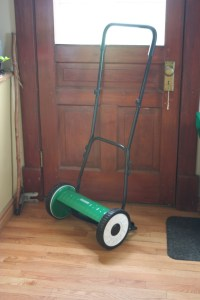 A push reel mower - spinning scythe blades mounted to an axle with a long metal handle for pushing
