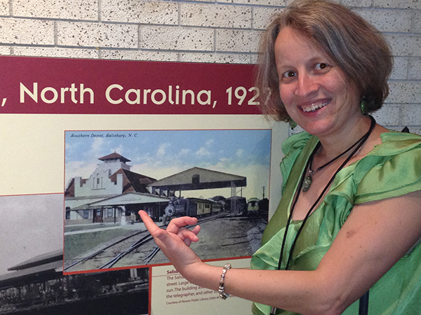 "Amanda Tomaini stands to the right of photo on the wall at the Museum of American History, pointing to a colorized black-and-white image of the Southern Depot in Salisbury, N.C. The words ""North Carolina, 1927"" can be seen above the picture."