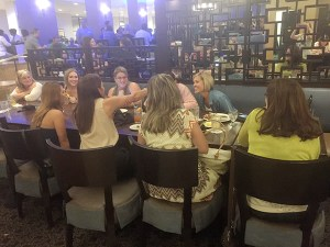 This picture shows a group of businesswomen around a large table in a restaurant, leaning in to look at a picture on a cell phone. The photo was taken during Sage Summit.