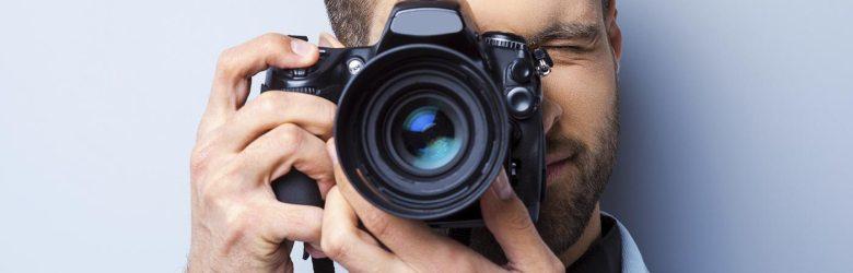 Man holding DSLR camera taking photo of you