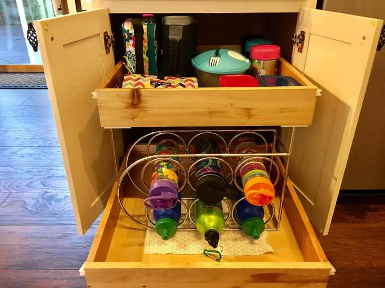 The top shelf in this low cabinet holds their lunch boxes, thermoses, and plastic containers. Wine rack for keeping water bottles organized and not falling over! A back to school routine should be simple so that it alleviates stress instead of adding more!Here are four routine ideas that will work for any family.~Practigal Blog