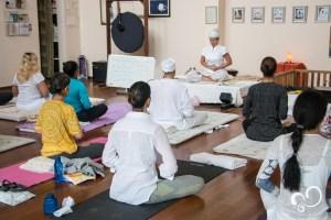 Praticantes de Kundalini yoga sentados para prática em salão de yoga durante Retiro espiritual