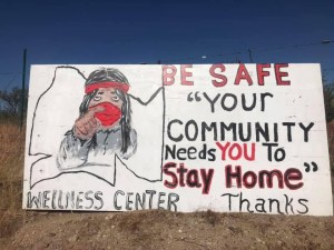 "A sign featuring the words: BE SAFE ""Your Community Needs YOU to Stay Home"" Thanks"