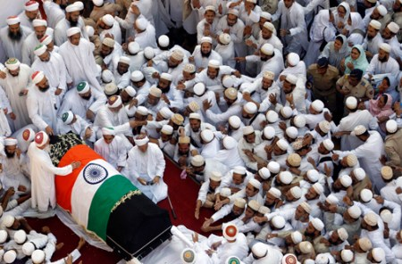Indian Muslims stretch out their hands towards the body of the head of the Dawoodi Bohra Muslim community Syedna Mohammed Burhanuddin during his funeral procession in Mumbai, India, Saturday, Jan. 18, 2014. A pre-dawn stampede killed more than a dozen people Saturday as tens of thousands of people gathered to mourn the death of Muslim spiritual leader Burhanuddin in the India's financial capital, police said. Burhanuddin died Friday at the age of 102. (AP Photo/Rajanish Kakade)