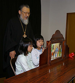 """Rector of the church in Sapporo Archpriest Alexis Matsudaira is helping Alexandra Yamaguti and Rebecca Sato show """"holy pictures""""."""