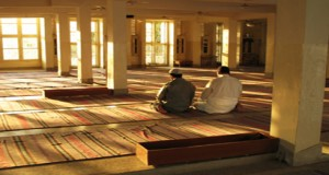 Two Muslim men are performing prayer.