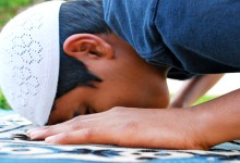 Young boy is Prostrating during Prayer.