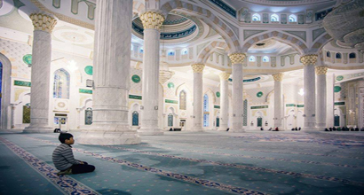 A young boy is waiting for the prayer at the mosque.