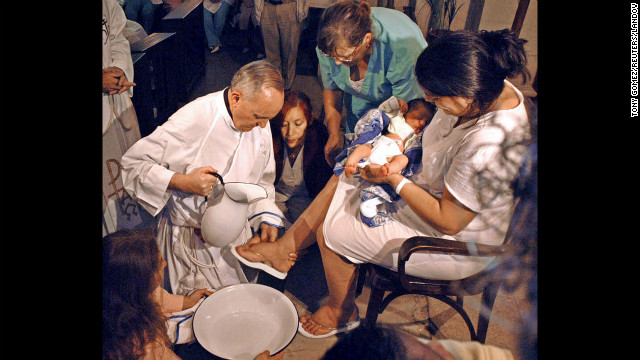 Cardinal Bergoglio (now Pope Francis I)  washing the feet of a woman in Buenos Aires.