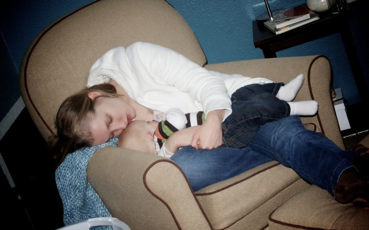 Baby and Mommy Sleep in Chair While Nursing