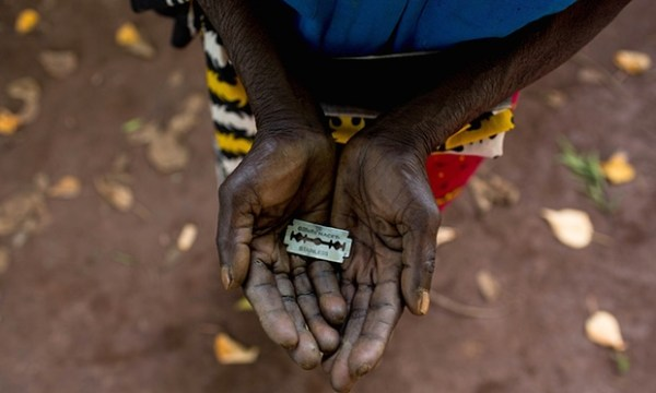 A woman in Mombasa, Kenya, shows the razorblade she uses to cut girls' genitals. Photograph: Ivan Lieman/Barcroft Media