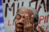 """A Filipina """"comfort woman"""" wipes away a tear during a January protest in Manila. Over 1,000 women and girls were captured and imprisoned in """"rape camps"""" in the Philippines by the Japanese military during World War II."""