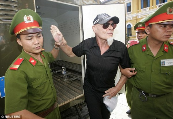 Prisoner: The singer flanked by police guards in Ho Chi Minh City in June 2006
