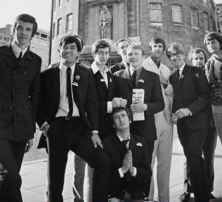 A group of the newly appointed Radio One DJ's pose outside Broadcasting House in 1967. (Left to right) Pete Drummond, Tony Blackburn, Dave Cash, Kenny Everett (kneeling), Duncan Johnson, Chris Denning, Ed Stewart, Mike Ahern, John Peel, unknown CREDIT: ROBERT STIGGINS/EXPRESS/HULTON ARCHIVE/GETTY IMAGES