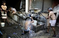 Indian migrant daily wage workers bath at a public well in New Delhi. New information shows that poverty in China and India is worse than previously thought. Photograph: Altaf Qadri/AP
