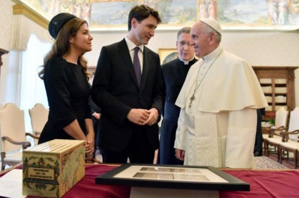 Pope Francis (right) exchanges gifts with Canadian Prime Minister Justin Trudeau (center) and his wife Sophie Gregoire-Trudeau (left) at the end of a private audience at the Vatican on May 29, 2017. AFP
