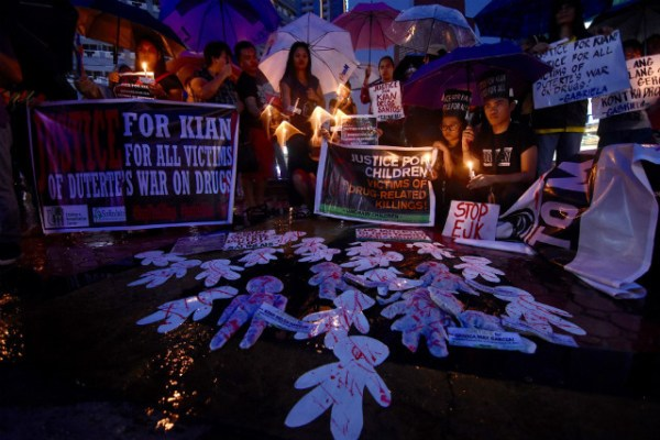 END KILLINGS. Protesters light candles and hold banners calling for an end to drug war killings in the Philippines. File photo by Maria Tan/Rappler