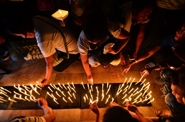 REMEMBERING THE DEAD. Relatives of victims of extrajudicial killings light candles in a prayer service at the Caloocan Cathedral on October 24, 2017. Photo by Maria Tan/Rapplerc