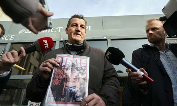 Fikret Alić holds a copy of Time magazine that featured his emaciated image on its cover in 1992. Photograph: Phil Nijhuis/AP
