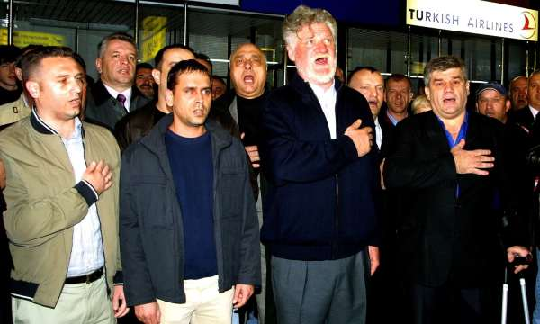 Slobodan Praljak, second from right, sings a Croatian hymn with former soldiers before his departure to the Hague tribunal in April 2004. Photograph: Antonio Bat/EPA