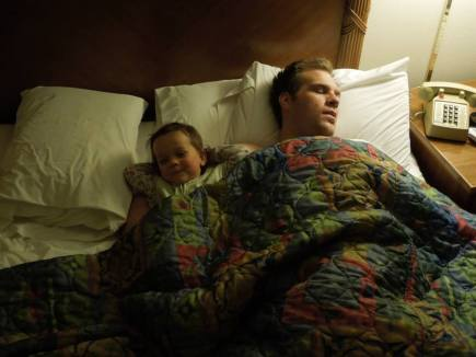 Dad and baby resting in motel room
