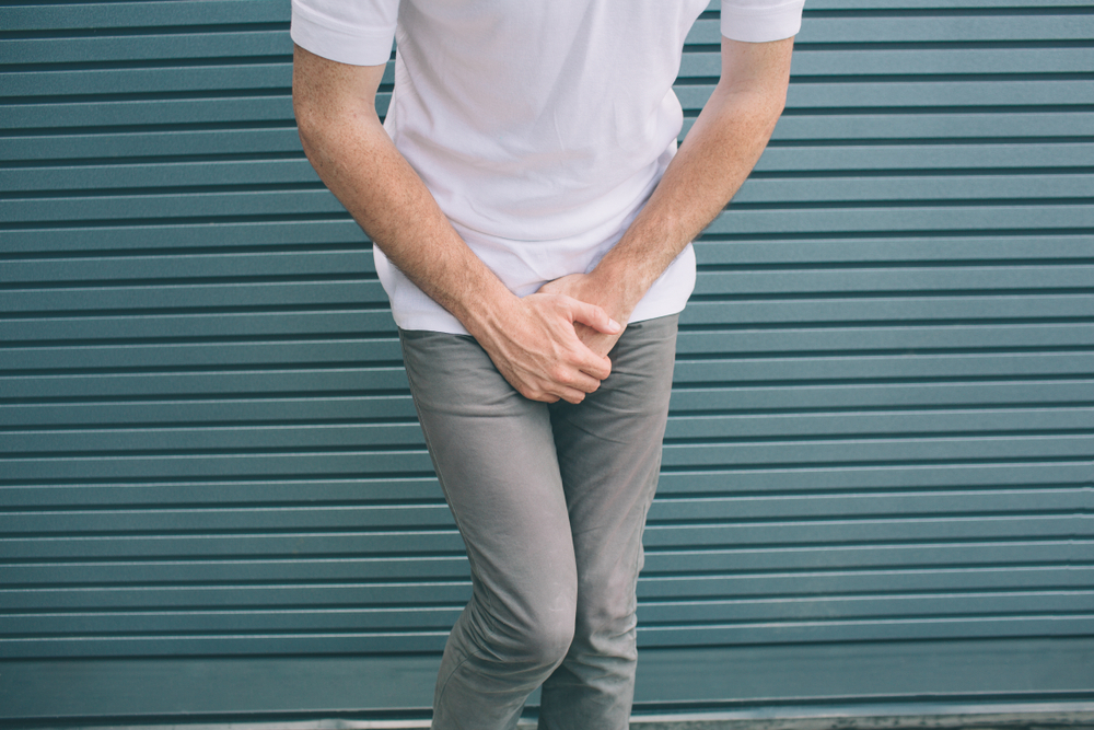 Man covering crotch area with hands
