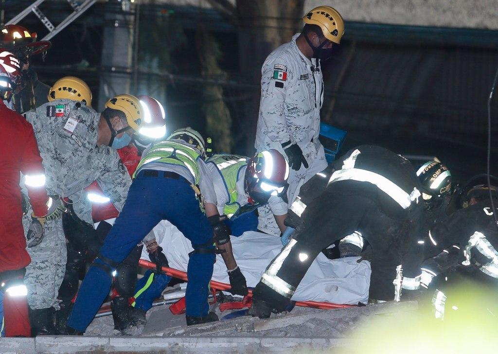 Miembros de los servicios de emergencia rescatan un cuerpo tras el colapso de los vagones del metro en la Ciudad de México. (Foto Prensa Libre: EFE)