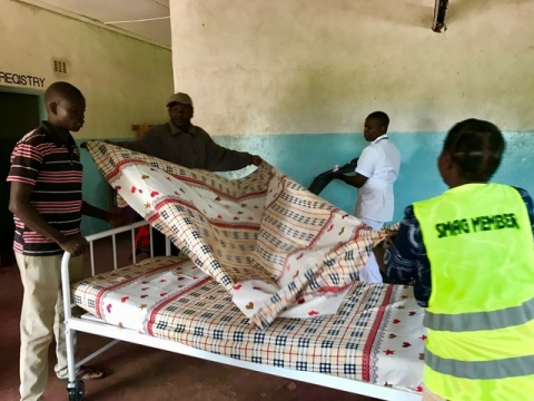 Egichikeni Rural Health Center staff putting the new bed linens on the beds.