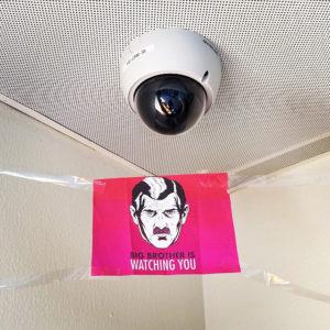 """Cámara de vigilancia y cartel con texto """"Big Brother is watching you"""""""