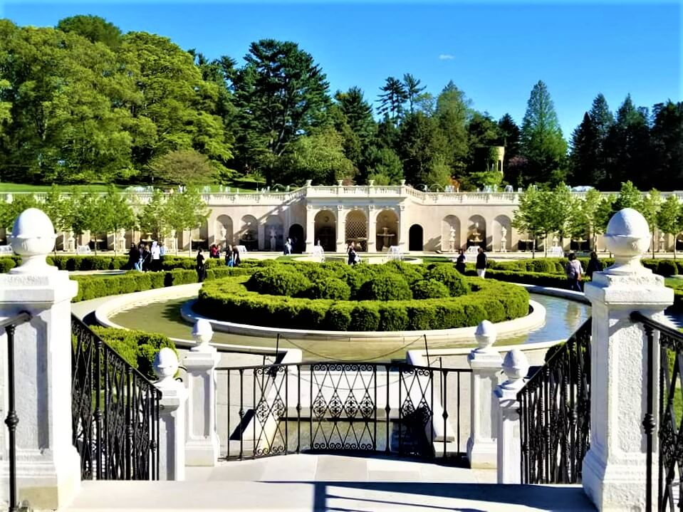 Metal rail fence in lower foreground and the main view is a center planting of round shrubbery in concentric circles, with a columns structure in the distance and trees beyond