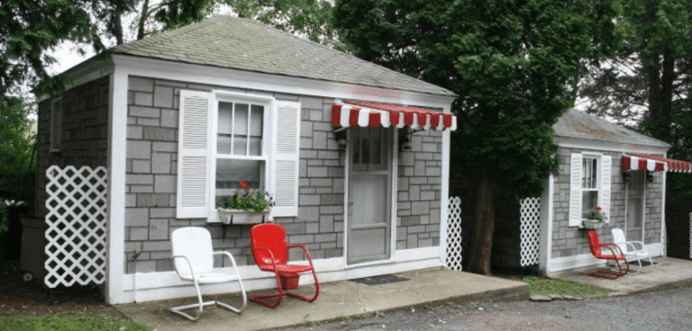 Two vintage motor court cabins, with metal red and white striped awnings, wait to greet new guests.