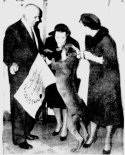 Mamie Eisenhower, right, tires to restrain Heidi as the dog jumps up on the director of the Tailwaggers Club of Washington, center. At left is Charles Hamilton of the Animal Rescue League. May 1958 photo by AP wire service.