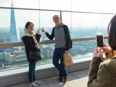 Tourists take photos from the external terrace at the Sky Garden in central London