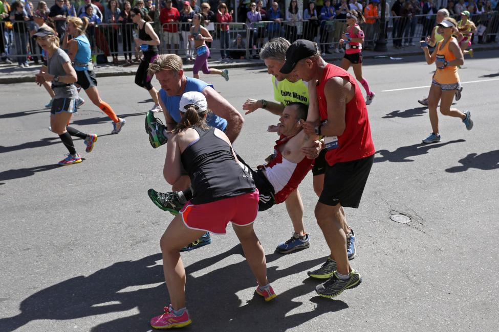 Four runners carry Hurst down Boylston Street during the 118th running of the Boston Marathon in Boston
