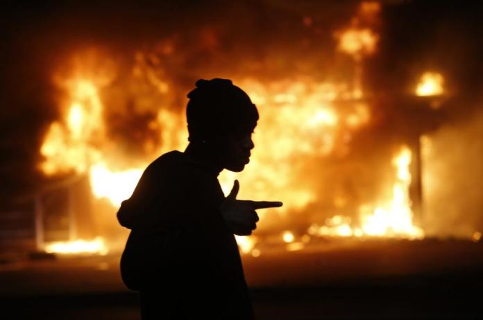 A man walks past a burning building during rioting after a grand jury returned no indictment in the shooting of Michael Brown in Ferguson, Missouri