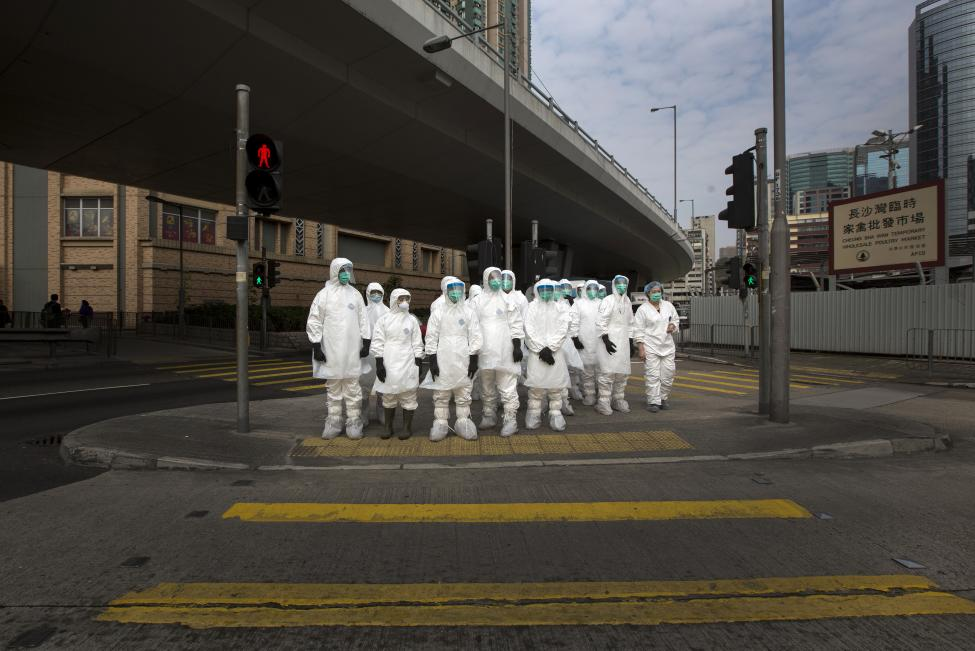 Health officers in full protective gear wait to cross a road near a wholesale poultry market in Hong Kong