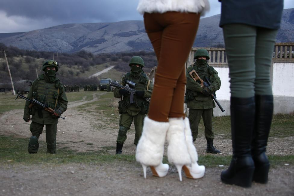 Local women watch armed men, believed to be Russian soldiers, assemble near a Ukrainian military base in Perevalnoe