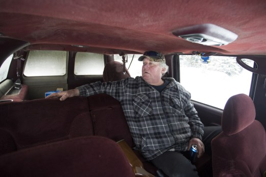 Carter McBreairty looks out the window from the backseat of his Suburban as he goes for a ride in the woods and has a cold beer.