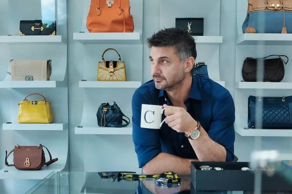 James Constantinou with designer handbags in background