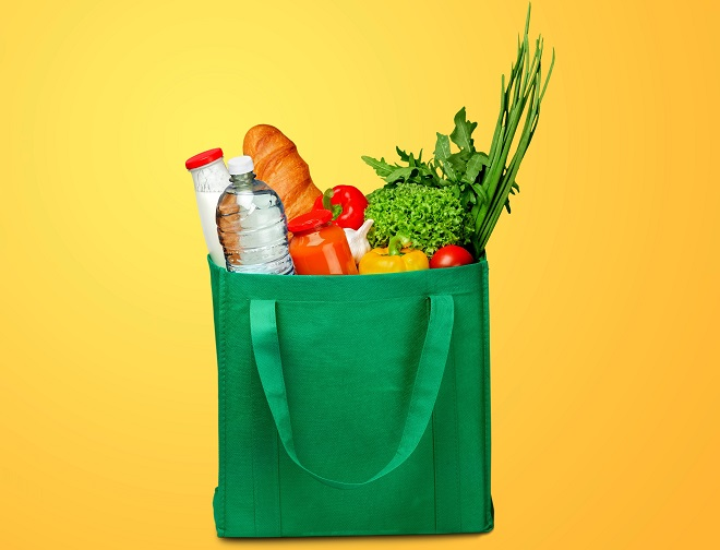 Bag full of groceries on wooden desk with pastel background