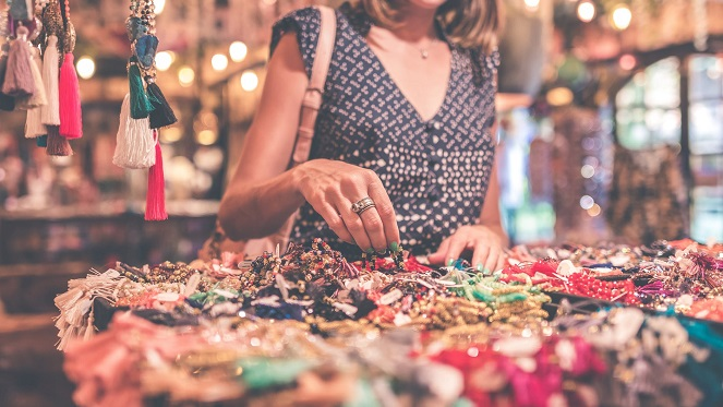 women browsing through market stalls looking at colourful jewellery