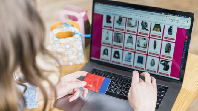 thrift shopping online computer screen and woman making a purchase with card