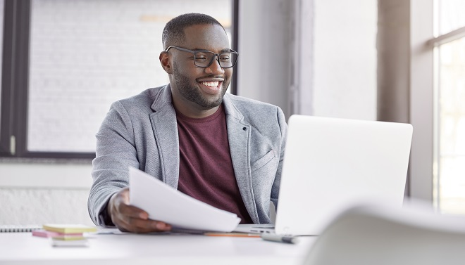 Smiling black male restaurater makes financial report and does shopping online, buys products for restaurant, studies annual figures, analyzes profits. Enterprise owner checks status of bank account
